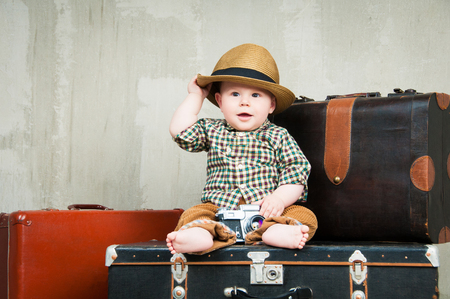 old photograph: Child sits on a suitcase and with a camera in his hands