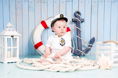 Little cheerful boy captain in the maritime interior