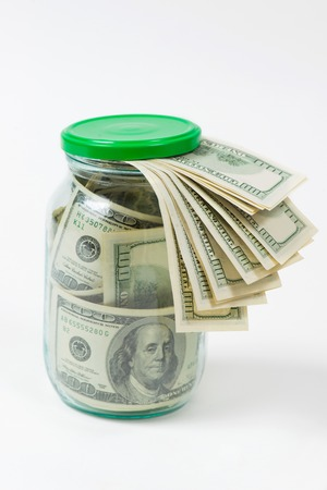 avidity: Many 100 US dollars bank notes in a glass jar isolated on white background Stock Photo