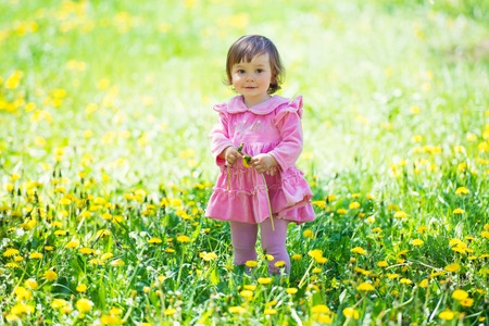 glades: Girl in pink dress with dandelion on green grass.