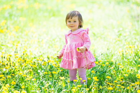 Girl in pink dress with dandelion on green grass.