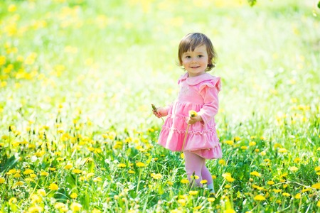 A little girl in a pink dress is laughing in a clearing with dandelions.