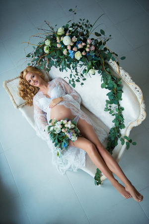 A stunningly beautiful red-haired pregnant girl with fresh flowers. Stock Photo