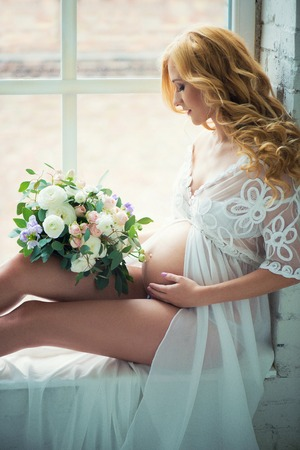 Beautiful red-haired pregnant girl sits on a window with a bouquet of flowers. Stock Photo