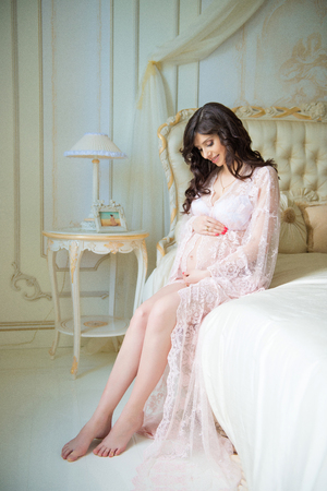 Beautiful pregnant girl in a lace negligee sitting on a bed of roses Stock Photo