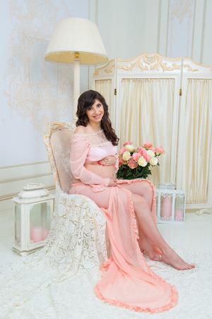 Beautiful motherhood. Pregnant in tender peach dress sits on chair