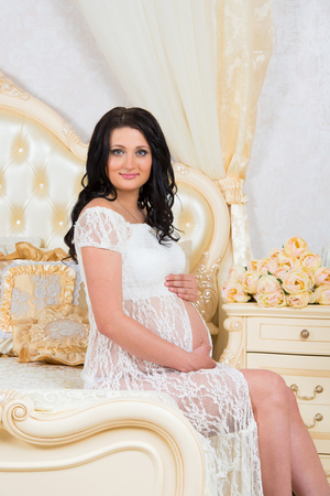 Smiling pregnant woman sitting on bed and hugging tummy Stock Photo