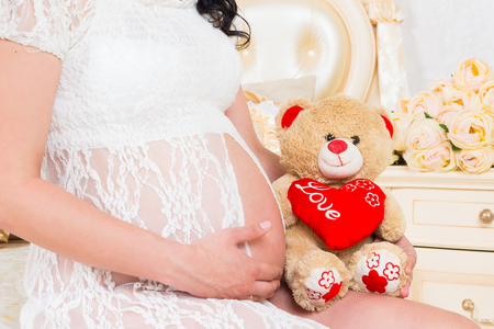 Pregnant in a white lace dress with teddy bear Stock Photo