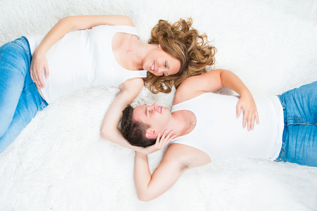 Beautiful pregnant young couple laying on top. Stock Photo