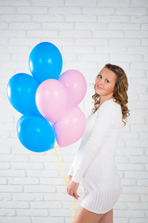 ninth: Happy pregnant woman with balloons in her hand, pink and blue.
