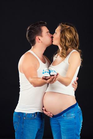 Esperando al bebé. Pequeños zapatos de bebé en las manos de papá en la panza de mi madre.