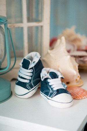 children s feet: Childrens jeans sneakers in the sea interior against the background of seashells. Stock Photo