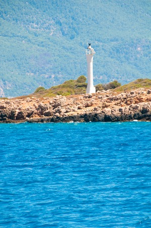 oil lamp: White Lighthouse on an island, view from the sea. Stock Photo