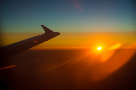 flight mode: Wing of a Airplane at sunset with clouds