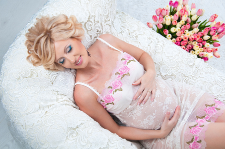 miraculous: Beautiful pregnant woman with luxurious hair black lying on the couch. Top view. Stock Photo
