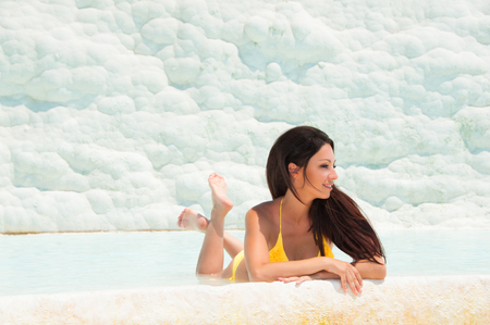 Beautiful brunette girl in yellow swimsuit in pamukkale. Province of Denizli in the south-west of Turkey.