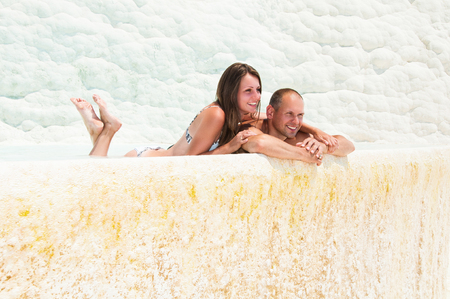 Young couple lies in the water, rest in Pamukkale. The province of Denizli in the south-west of Turkey.