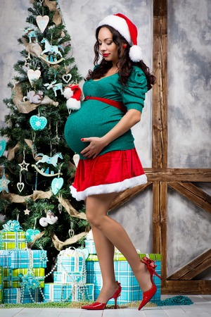 pregnant girl in pin up suit near a christmas tree stock photo 81116233