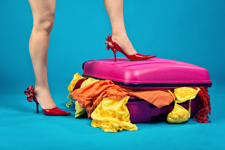 messy clothes: Ladys leg on a stuffed suitcase. We pack things on a long trip. Travel is preparation