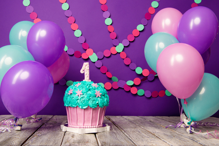First birthday cake with a unit on a purple background with balls and paper garland.