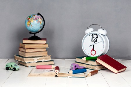 yellow notepad: Alarm clock, books, toys and globe on a gray background. Stock Photo