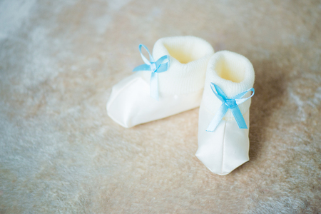 Baby booties with blue ribbons. Waiting for the boy