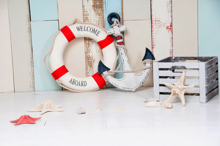 painted wood: Composition on a marine theme with an anchor and life buoy, seashells and starfish on a wooden background. Stock Photo