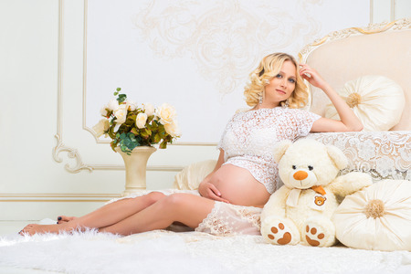 bear s: Young pregnant girl sitting near white sofa with teddy bear and looking at pregnant belly Stock Photo