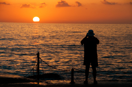 man is photographing a sunset against the background of the sea. Stock Photo