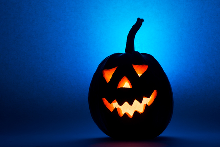 Halloween pumpkin, silhouette of funny face on blue background. Фото со стока