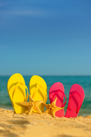 Sea-stars with yellow and pink sandals stand in the sand against the background of the sea. Stock Photo