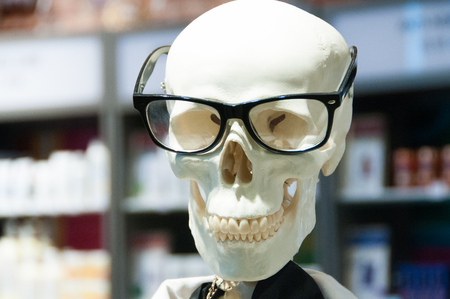 Skull head wearing eyeglasses and white scientific lab coat.