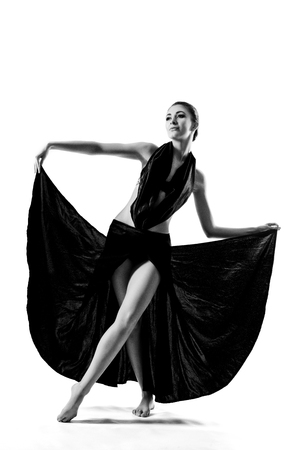 A beautiful athletic girl in a black dress is dancing