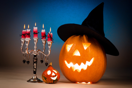Halloween pumpkin with a candlestick, funny face face on a blue background. Stock Photo