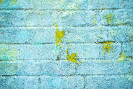 Background and wallpaper or texture of a blue brick wall with stains of yellow paint