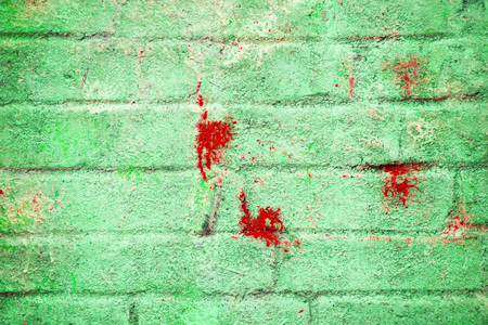 Background and wallpaper or texture of a green brick wall with stains of red paint