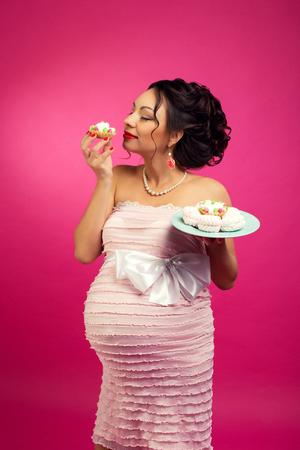 Portret van een hongerige gelukkige zwangere vrouw die een zoete cake eet, die op een roze achtergrond wordt geïsoleerd.