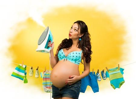 Mujer embarazada con hierro en el fondo de la ropa para niños. Pin y esperar al bebé Foto de archivo - 89174762