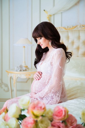 Smiling pregnant woman sitting on bed and hugging tummy.