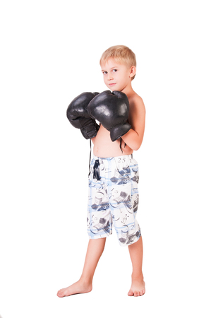 Boy in boxing gloves is isolated on white background. Stock Photo
