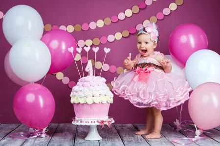 portrait d & # 39 ; une petite fille d & # 39 ; anniversaire gaie avec le premier gâteau . la première fille attraper le gâteau à tartiner . gâteau