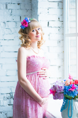 Pregnant woman smiling, looking at belly, holding flowers. Pink dress.