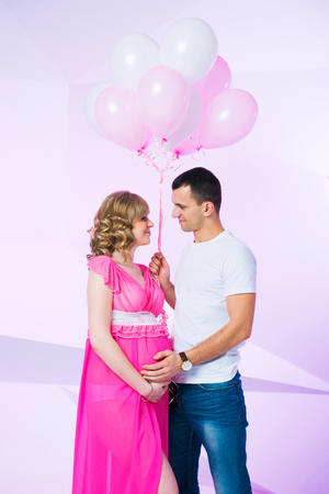 Beautiful and happy couple waiting for their daughter, standing in the studio with balloons on a pink background.
