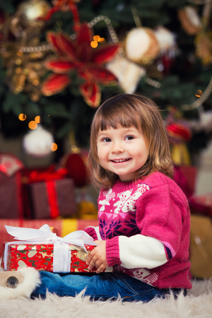 Happy girl with a gift in hands on a background of a New Year tree