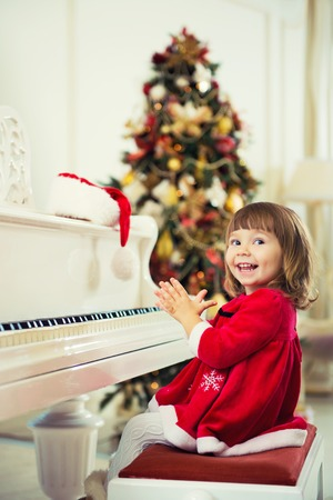 Little beautiful girl is playing on a white grand piano.