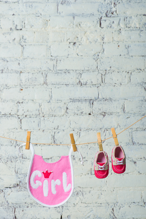 Childrens toddler pink saliva and red shoes on a rope against a white brick wall.
