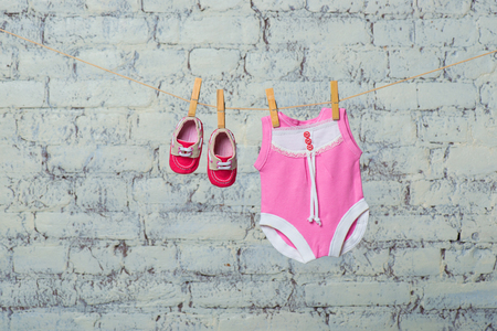 Childrens pink body, bib and red shoes, dry on a rope against a white brick wall.