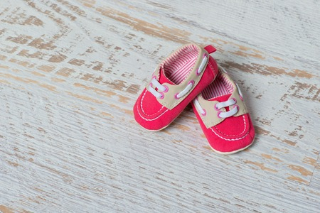 Baby red shoes on a rope against a white brick wall.
