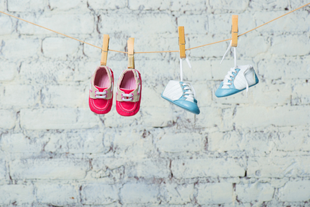 Baby blue and red shoes on a rope against a white brick wall. Stock Photo