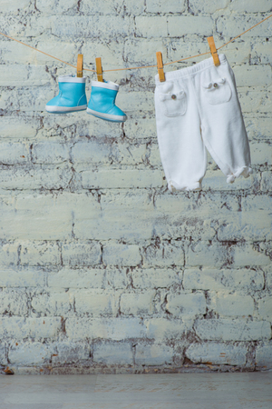 Childrens boots and pantyhose dry on a rope against a white brick wall.